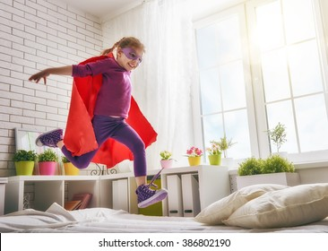 Child girl in an Superman's costume plays. The child having fun and jumping on the bed.