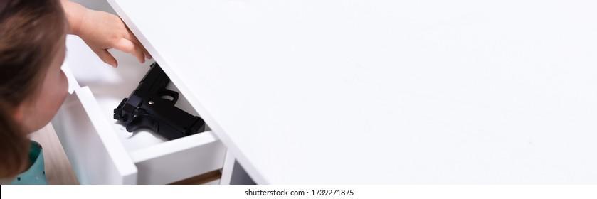Child Girl Taking Gun From Drawer. Home Safety