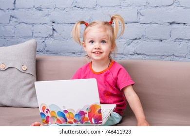 child girl three years old uses for training laptop computer sitting on couch indoors with blue brick wall. A baby with blue eyes and a blonde with funny tails on her head