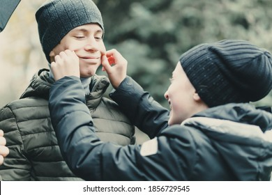 child girl touching boy face with her hands and making smile, emotionless teenager stand with umbrella, autumn season, city street, don't worry be happy