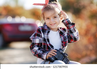 child girl traveler. trip alone. girl walking with camera and suitcase on autumn nature. travel, vacation, holidays
