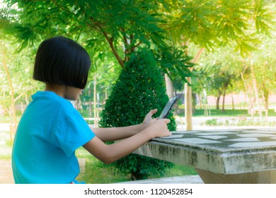 Child girl used smartphone to playing game and search information from internet at the park. Education and technology concepts.