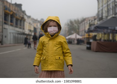 Child girl walking outdoors with face mask protection. Kindergarten kid breathing through medical mask because of smog and air pollution.
