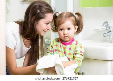 Child girl washing her hands in bathroom. Mom helps her little daughter.