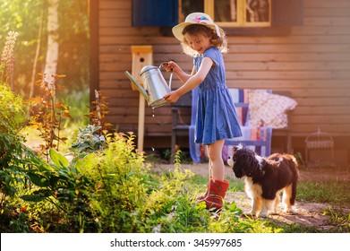 child girl watering flowers with her dog in summer garden, little helpers, outdoor activities on vacation