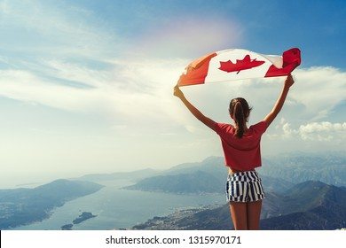 Child girl is waving Canadian flag on top of mountain at sky background