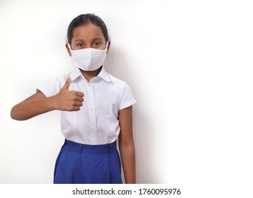 Child girl wearing mask with school uniform doing thumb up. Isolated white background.