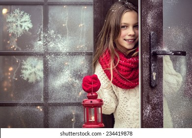 Child girl welcome guests and holding holiday lantern, snow weather, house is decorated before Christmas
