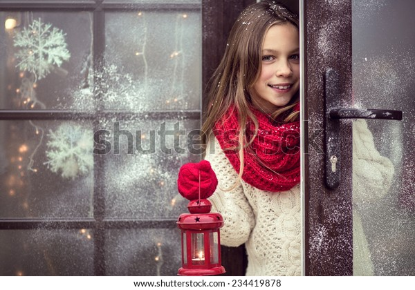 Kindermädchen willkommen Gäste und hält FeriLaterne, Schnee Wetter, Haus ist vor Weihnachten geschmückt