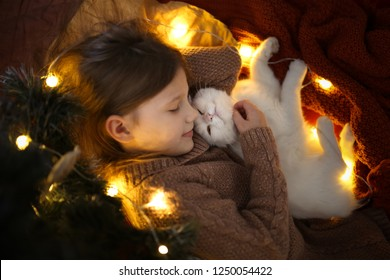 Child girl and white cat lie snugly under the Christmas tree in a real house, New Year and Christmas concept
