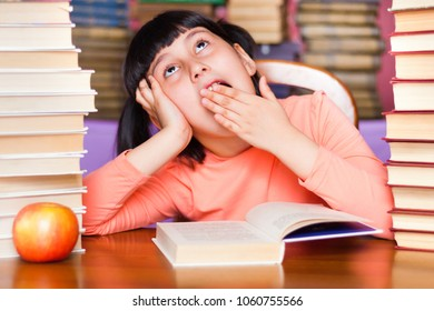 Child girl yawns in library while preparing to school test. Bored schoolgirl while cramming. Exhausted kid among books.