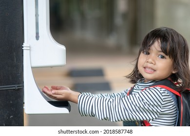 Child girls kid using automatic alcohol gel dispenser spraying on hands sanitizer machine antiseptic disinfectant, new normal life after Coronavirus COVID-19 pandemia.