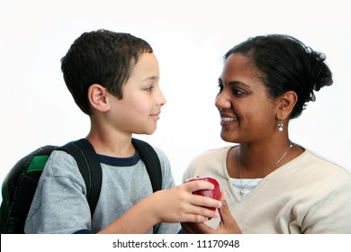 Child giving apple to his teacher