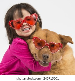 Child giving hug to dog. Both wearing heart shaped shades.