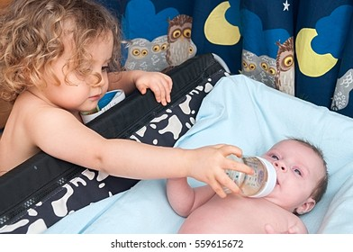 child giving a water to little sister