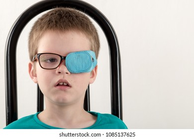 Child in glases with Occluder. Ortopad Boys Eye Patces nozzle for glasses for treating strabismus (lazy eye)