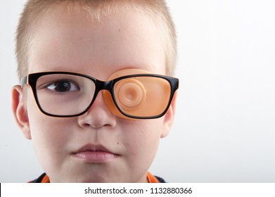 Child in glases with Occluder. Ortopad Boys Eye Patces nozzle for glasses for treating strabismus (lazy eye). Copy space for text