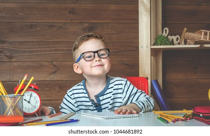 Child in glasses doing his homework with alarm clock on the table. Happy smiling boy in glasses at school. Child in elementary school. Kid indoors at home in kids room interior with wooden background.