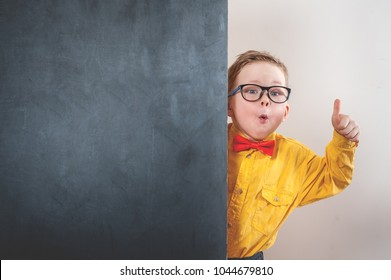 Child in glasses holding chalkboard blank with thumb up. Happy kid in butterfly tie in class. Back to school. Success, bright and creative ideas, innovation technology and education concept.