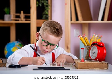 Child in glasses learning math and numbers in class. Kid reading a book while sitting on desk. Pupil holding pen and writing in notebook. Back to school. Student doing test in primary school.