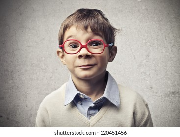 Child with glasses is surprised by something or someone