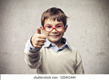 Child with glasses thumbs up