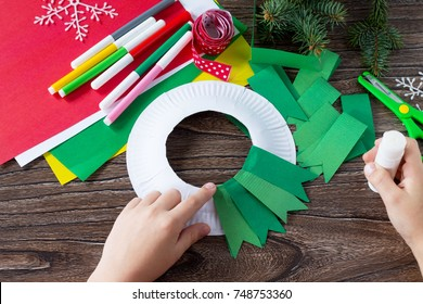 The child glues the details of the Christmas wreath with a candle. Made by own hands. Children's art project for children. Craft for kids.