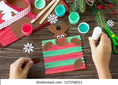 The child glues the parts Santa and Reindeer stick gift. Handmade. Project of children's creativity, handicrafts, crafts for kids.