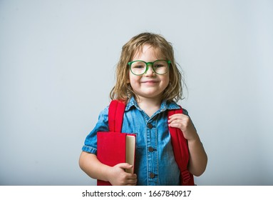 Child go back to school with backpack and book. Kid in eyeglasses has idea. Happy pupil.