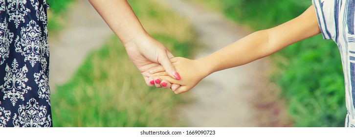 child goes hand in hand with his mother. Selective focus. nature.