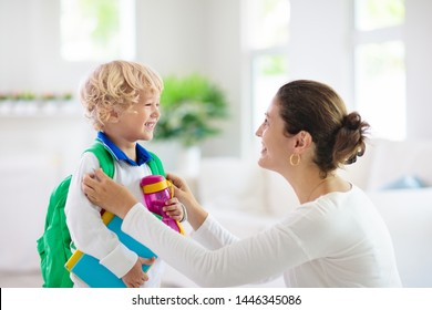 Child going back to school. Mother and kid getting ready for first school day after vacation. Little boy and mom going to kindergarten or preschool. Student packing books, apple and lunch in backpack.