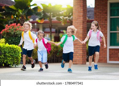 Child going to school. Boy and girl holding books and pencils on the first school day. Little students excited to be back to school. Beginning of class after vacation. Kids eating apple in school yard - Shutterstock ID 1780497341