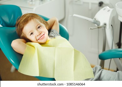 Child in good mood sitting on chair and without fear waiting dentist. Young boy is going to treat teeth. caries, fillings, teeth