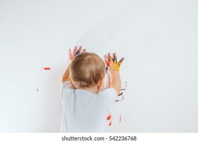 The child got dirty colors, draws on the wall