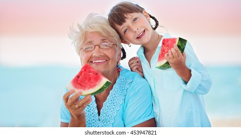 child and grandmother eating watermelon on the beach