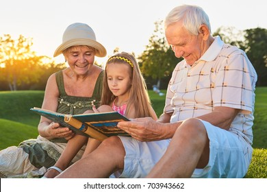 Child with grandparents, photo album. Happy people looking at photos.