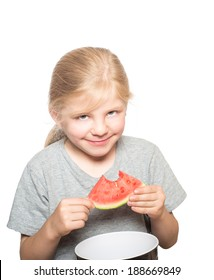 Child with gray eyes and blond hair looking mischievous eating watermelon isolated on white