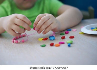 a child in a green T-shirt makes jewelry with his own hands stringing multi-colored beads on a thread