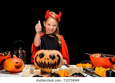 child in halloween costume of devil with jack o lanterns and sweets, isolated on black