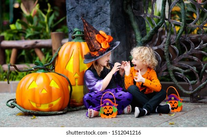 Child in Halloween costume. Kids trick or treat. Little boy and girl dressed as witch with hat holding pumpkin lantern and candy bucket. Family celebration.