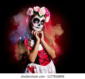 Child in a  Halloween sugar skull outfit covered with smoke
