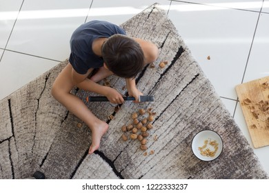 child is hammering nuts on the floor. crack nuts