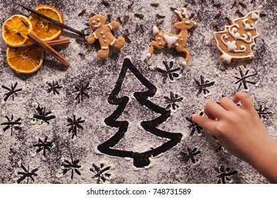 Child hand drawing holidays scene with xmas tree and stars in the flour prepared for the christmas cookies, shallow dept