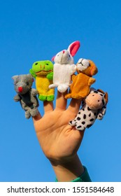 child hand with finger dolls: cow, frog, dog, rabbit, mouse, hare. animal finger puppets show and theater. Kid playing fingers puppets.