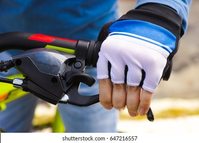 Child hand with glove on handlebars with brake lever. Close-up.