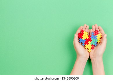Child hand holding colorful heart on green background. World autism awareness day concept