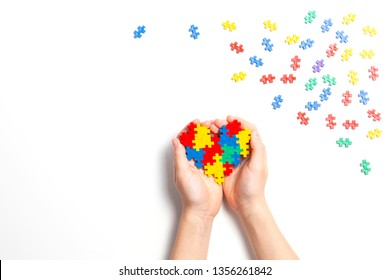 Child hand holding colorful heart on white background. World autism awareness day concept
