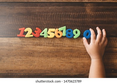 Child hand holding number zero with sets of other colorful numbers plastic toy on a wooden table. Concept of child learning numbers and child education