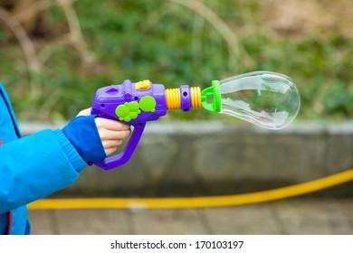 Child hand holding the soap bubble gun
