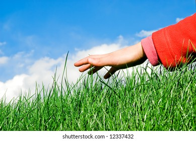child hand moving ahead above the grassy surface